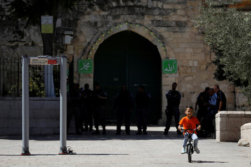 Boy rides his bicycle next to a newly installed metal detector at compound in Jerusalem's Old City