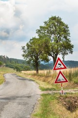 Road warning sign on slippery road. Spilled gravel on the road. Country road in the Czech Republic.