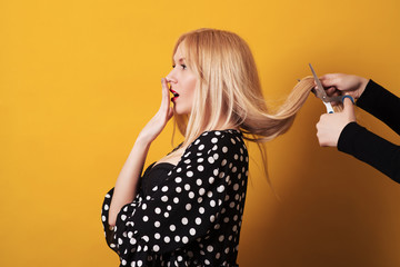 Blonde young woman with long hair doing hairstyle. Scissors cut the girls hair.