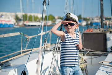 cute little boy captain wearing captain cap and sunglasses aboard luxury boat