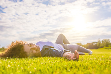 The happy woman lay on the grass against the background of the sunshine Wall mural