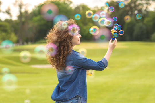 The attractive woman blowing bubbles in the park