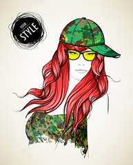 A girl in a camouflage baseball cap and yellow glasses. Fashion girl.
