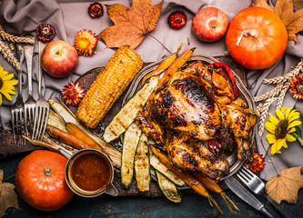 Thanksgiving dinner table with Roasted whole turkey ,sauce with grilled autumn vegetables,corn ,cutlery , decoration pumpkin, autumn leaves and flowers arrangements on rustic background, top view.