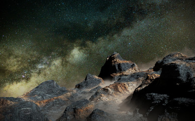 rocky landscape with low crawling fog lit by the Milky Way galaxy