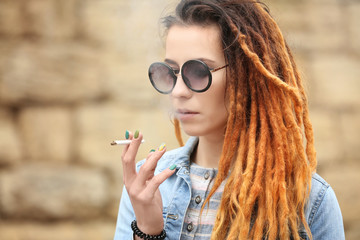 Young beautiful woman smoking weed on blurred background