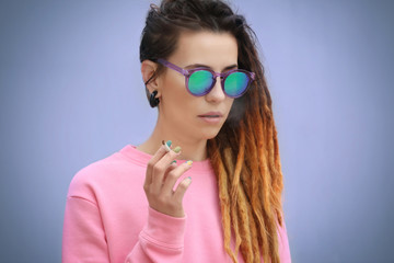 Young beautiful woman smoking weed on light background