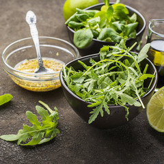 Ingredients for salad: rucola, root salad, olive oil, limes on a dark background. Seasonal Healthy Eating.