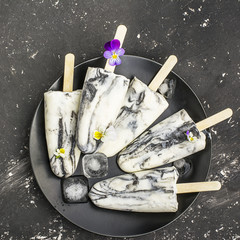 Yoghurt refreshing marble ice cream popsicle in trendy fashion colors on a dark background with edible flowers of garden violas. Selective focus. Top View
