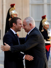 French Prsident Emmanuel Macron greets Israel's Prime Minister Benjamin Netanyahu as he arrives at the Elysee Palace in Paris