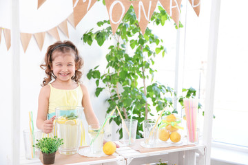Cute little girl selling lemonade at counter