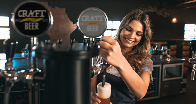 Female bartender tapping craft beer in bar