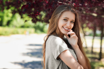 A beautiful blonde on a light sunny background. An adorable girl relaxing and laughing outdoors.  A posing young woman in a park.