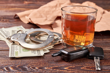 Whiskey, handcuffs, car key, money. Booze driving concept.