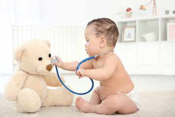 Cute little baby with stethoscope and toy bear playing at home. Health care concept