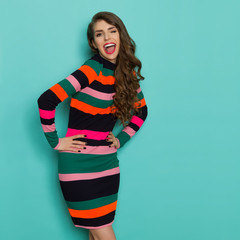 Laughing Young Woman In Vibrant Dress Is Winking