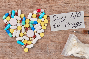 Say NO to Drugs. Heart from colorful pills, message, drugs, wooden background.