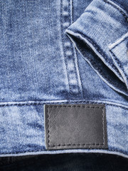 Classic blue denim closeup for background with empty leather label and a sleeve