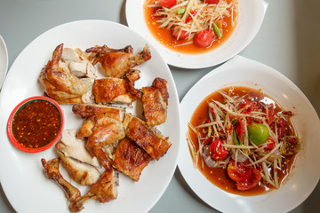 grilled chicken with thai sauce and papaya salad or spicy salad of thailand on white plate