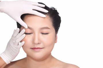 Beautiful Plus Size woman female face in the hands of a doctor cosmetologist gloves. checking before treatment, copy space for text logo