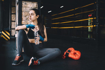 Young woman sitting on the floor after hard workout in gym.