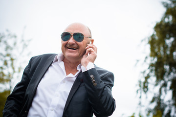 Mature stylish man in classic costume and sunglasses talk to telephone