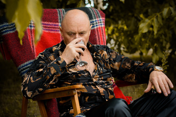 Mature stylish senior in his garden sit in red plaid armchair and tasting red wine