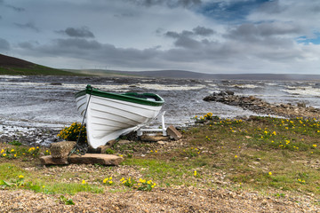 Rowing boat on shore of a stormy Scottish Loch, Orkney UK