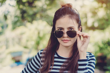 Woman Hipster with sunglasses Fashion Style Lifestyle Concept, wearing a black and white striped t-shirt.