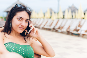 Beautiful woman using mobile phone on the beach