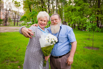 Elderly couple in love stands together with flowers in a park an