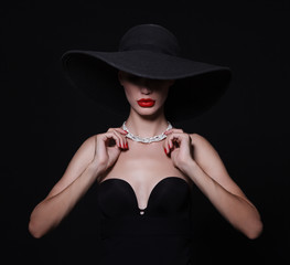 A necklace of diamonds on the neck of a luxurious woman in a hat.