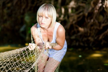 Woman in river. White t-shirt, fishnet