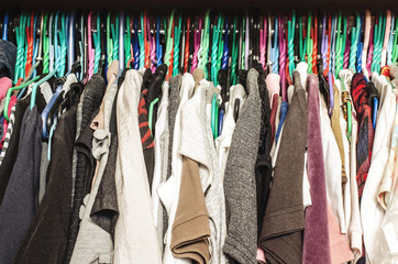 Fashion clothes on clothing rack - bright colorful closet. Close up of rainbow color choice of trendy female wear on hangers in store closet . Summer home wardrobe.