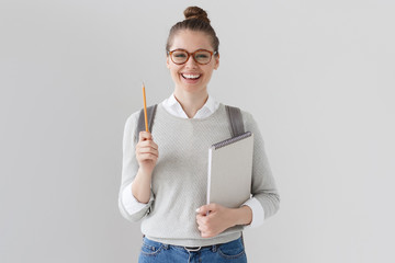 Studio shot of positive student girl isolated on grey background wearing glasses, sweater and jeans, backpack, pointing up with pencil, holding notebook, looking excited, full of energy and ideas.