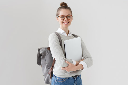Indoor photo of college student girl isolated on gray background, smiling at camera, pressing laptop to chest, wearing backpack, ready to go to studies, start new project and suggest new ideas.