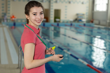 swimming coach with whistle and stopwatch near poolside, looking at camera
