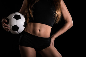 Torso of a sexy woman with a football