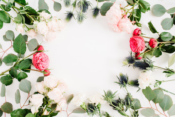 Round frame wreath made of red and beige rose flowers, eringium flower, eucalyptus branches and leaves isolated on white background. Flat lay, top view. Floral background