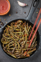 Spicy salad of fern with onion, garlic, soy sauce and spices. Dish Eastern and Asian cuisine. Selective focus