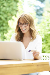 Paying online. Shot of a happy mature woman relaxing outdoor and using a bank card and laptop while shopping online.