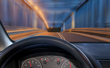 A view of the cockpit of a car driving at night through an illuminated bridge