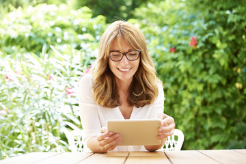 Happy woman with digital tablet outdoor