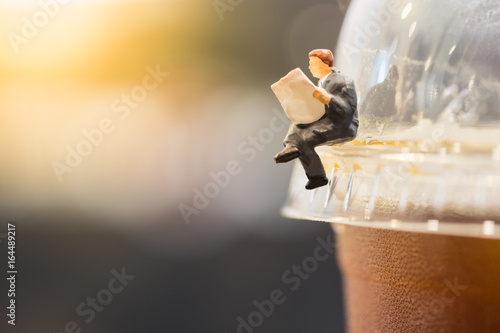 Reading, relaxing, hobby concept. Close up of businessman miniature mini figure sit and read newspaper on a take away plastic cup iced black coffee (Americano)