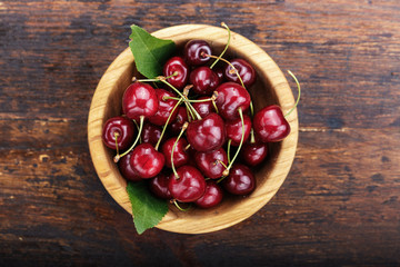 Ripe cherries in a wooden plate