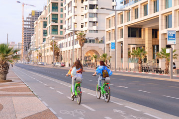 TEL AVIV, ISRAEL- APRIL, 2017: Herbert Samuel st. bike track and walking area for pedestrians in the center of Tel Aviv. Girls ride bicycles on holiday