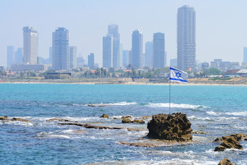 TEL AVIV, ISRAEL - APRIL, 2017: The flag of Israel against the background of modern Tel Aviv, the Mediterranean Sea.