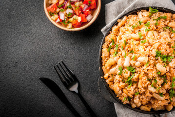 Mexican, Latin American cuisine. Mexican Rice and Beans Bowl- recipe made with rice and white beans, homemade, with fresh herbs and herbs. In a frying pan for cooking, with salsa, top view copy space
