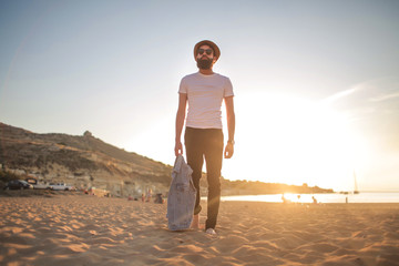 Handsome hipster guy walking in a beach