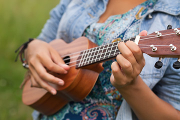 Young hipster woman playing on Ukulele outdoors